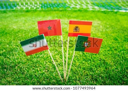 Group B - Portugal, Spain, Morocco, IR Iran - National Flags on green grass on football stadium #1077493964