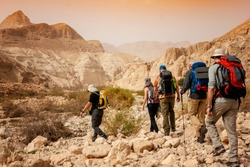 Group backpackers people traveling descending desert trail stone cliffs, hiking mountains Negev