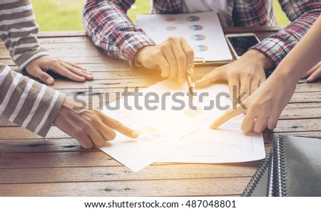Group business  meetings style sitting at natural country style wooden desk on green background,selective focus on finger