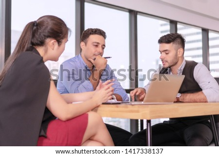 Group businesspeople colleagues talking about planning project in the workplace. Man holding pen with colleagues sitting on desk with laptop while talking work together in office on city background. #1417338137