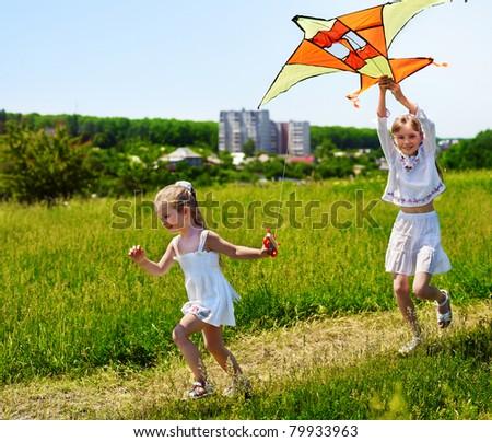 Group children flying kite outdoor.