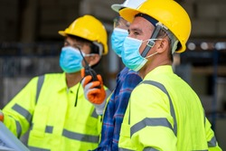 Group civil engineer wearing protective face mask during the inspection in construction site,Coronavirus has turned into a global emergency.