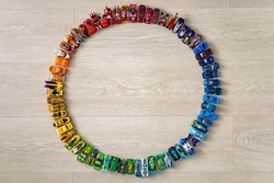 Group colorful childish car toy hot wheels in accuracy circle on wooden floor top view. Collection of modern miniature automobile playthings, many sport vehicle model transport for hobby and leisure