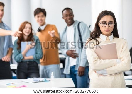Group Conflict. Sad latin woman in eyeglasses standing away alone, suffering humiliation and public disgrace, crowd of bad people bullying pointing fingers at victim, laughing. Discrimination, Gossip Foto stock ©