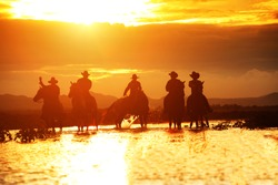 Group cowboy  on horseback :Silhouette of a group of cowboy sitting on his horse at sunset river background