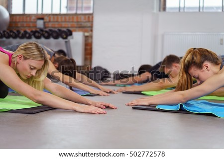 Group doing joga on floor of exercise gym while side by side on yoga mats Stock fotó ©