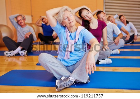 Group doing stretching exercises in back training class in a fitness center #119211757
