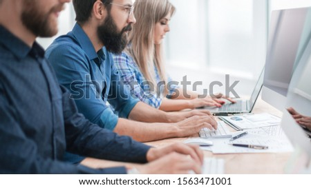 group employees using computers to analyze incoming information