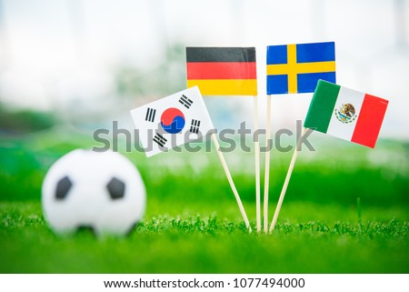 Group F and football ball on green grass. National Flags of Germany, Mexico, Sweden, Korea Republic, South Korea #1077494000