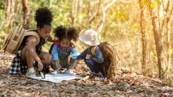 Group family children checking map in the jungle adventure.   Asia people tourism for destination leisure trips for education and relax in nature park background.  Travel vacations and Life Concept