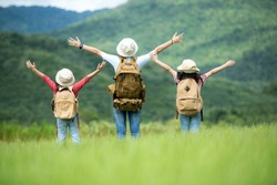 Group family children travel nature trips raise arms and standing see mountain outdoors, adventure and tourism for destination leisure trips for education and relax in nature park. Travel vacations