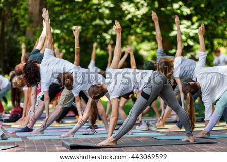 Group free yoga class for people of different age and gender in the city park. International Day of Yoga, summer