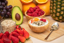 Group Fruits mixed with banana, orange, strawberry and nuts, concept health food and diet, vegetarian food in the top view on the wood table.