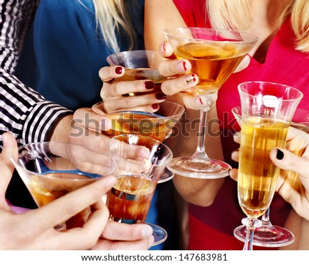 Group hand holding glass of beverage.