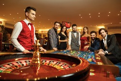 Group happy friends make bets gambiling at the roulette table in the casino.