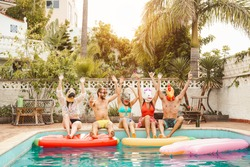 Group happy friends making pool party - Young people having fun celebrating carnival event in exclusive swimmingpool summer tropical vacation - Friendship and youth holidays lifestyle concept