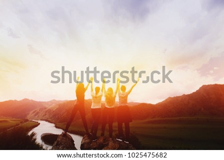 Group happy friends up hand on background mountains, sunset