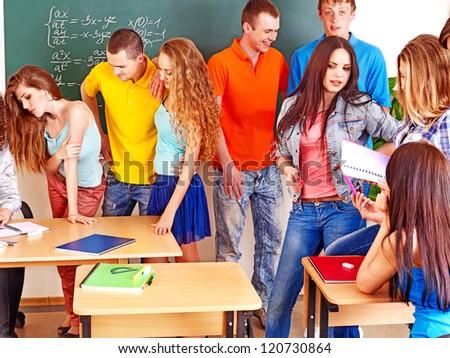 Group happy student in classroom near blackboard.