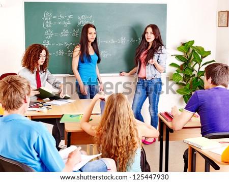 Group happy student near green  blackboard in classroom.