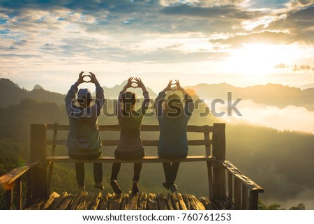 Group happy tourists on top of a mountain enjoying valley view before sunrise,
