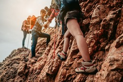 Group Hiker team helping her friend climb up the last section of sunset in mountains. Traveler teamwork walking in outdoor lifestyle adventure and camping.Teamwork,Travel Concept.
