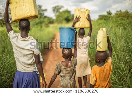 Group if young African kids walking with buckets and jerrycans on their head as they prepare to bring clean water back to their village.