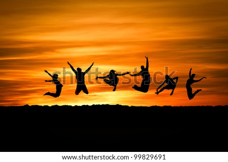 group jumping in sunset at beach