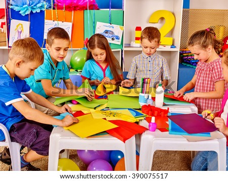 Group kids holding colored paper on table in kindergarten. Kids learning do origami.