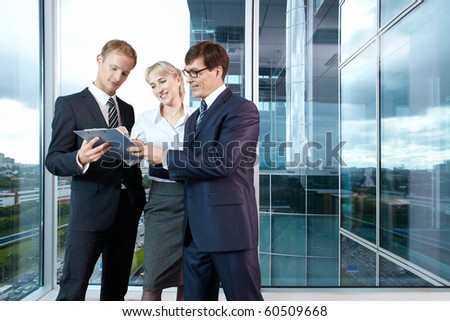 Group members are discussing something in the background of a large window in the office