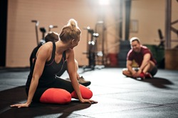 Group of a fit young people in sportswear talking together while sitting on the floor of a gym after a workout