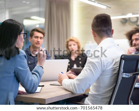 Group of a young business people discussing business plan at modern startup office building - Shutterstock ID 701565478