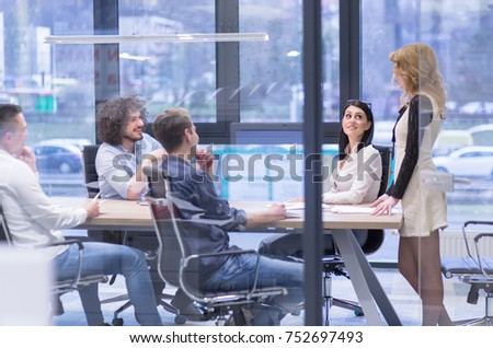 Group of a young business people discussing business plan at modern startup office building #752697493