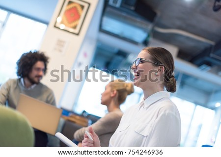 Group of a young business people discussing business plan at modern startup office building - Shutterstock ID 754246936