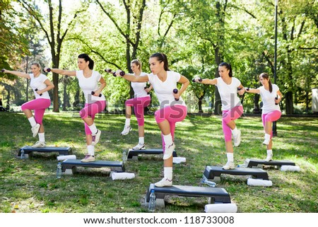 group of a young women doing exercises with dumbbell on a sunny day