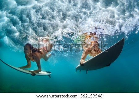 Group of active girls in action. Surfer women with surf board dive underwater under breaking big wave. Healthy lifestyle. Water sport, extreme surfing in adventure camp on family summer beach vacation #562159546