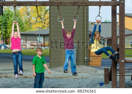 Group of active kids playing at a school playground. - stock photo