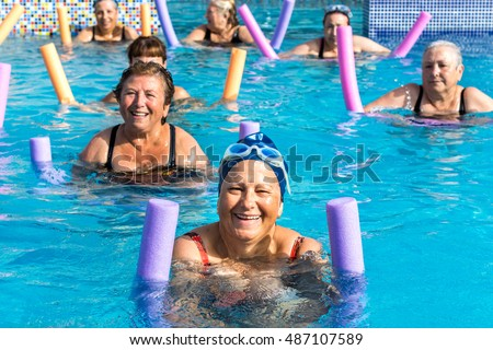 Group of active senior women doing aqua gym in outdoor swimming pool.
