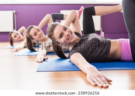 Group of active smiling women are training in fitness club. Smiling and looking at the camera.