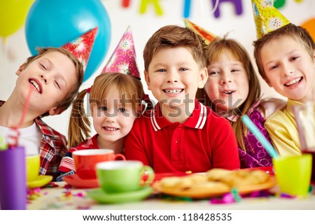 Group of adorable kids looking at camera while having fun at birthday party - stock photo
