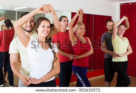 Group of adult american people dancing salsa in studio