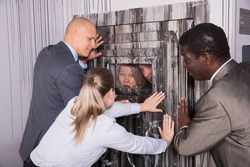 Group of adult men and women trying to get out of escape room stylized like thriller