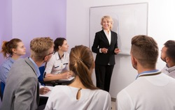 Group of adult students attentively listening to lecture of female teacher in classroom