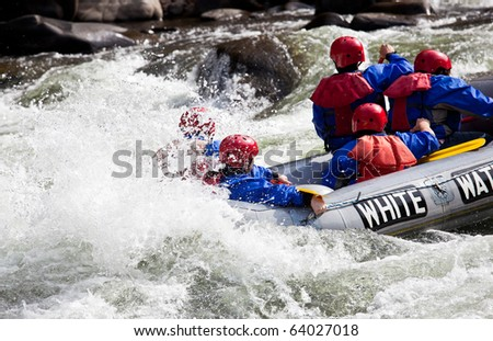 Group of adventurers in an inflatable dinghy in the white water of a fast moving river