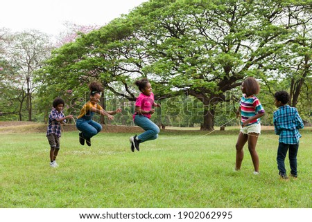 Group of African American children having fun jumping over the rope in the park. Cheerful kid jumping over the rope outdoor. Happy black people enjoying playing together on green grass