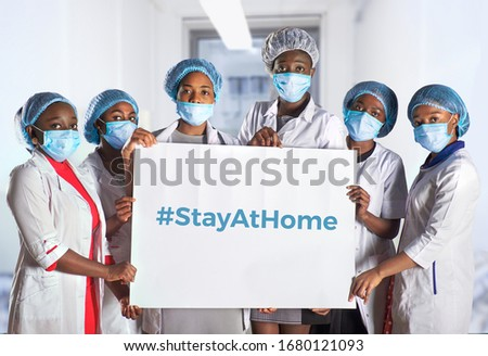 Group of African women nurses activists in face mask, hand sign plackard, caption hashtag StayAtHome. Group of medics, message for social media. Information alert to stay at home to flatten the curve.