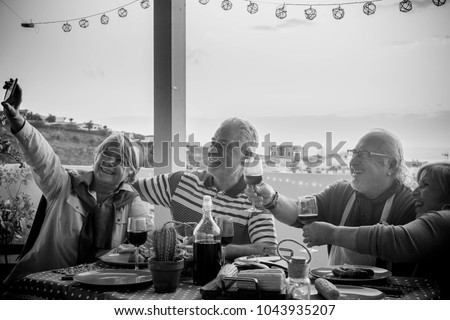group of aged senior friends adults having dinner and doing party nice time in the rooftop terrace outdoor with wine and food. having fun during the sunset with beautiful sun backlight and Nice view