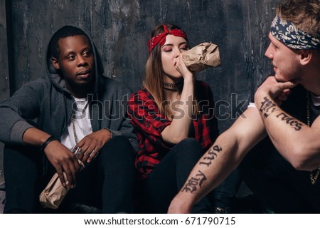 Group of alcoholic young people on night party. Youth addiction problem. Tired drunk caucasian girl drink alcohol from bottle, sad guys with tattoo sits near . Students lifestyle Сток-фото ©