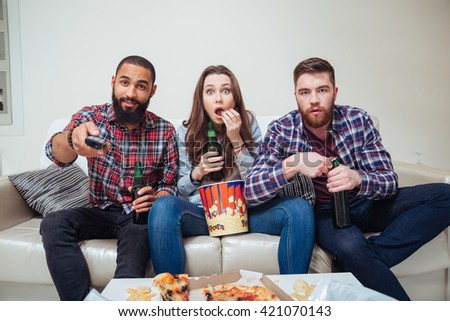 Group of amazed shocked young friends watching tv and eating popcorn on sofa
