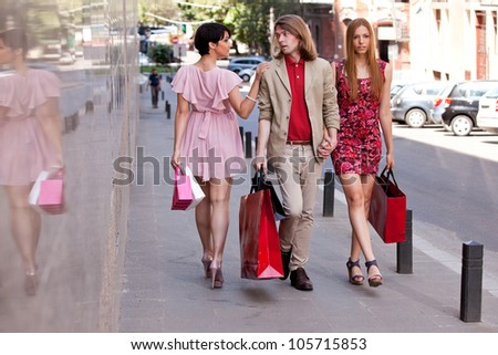 Group of an handsome young man with two beautiful women with colorful shopping bags on the street. Concept for temptation