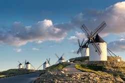 Group of ancient windmills in the town of Consuegra (Spain), on the route of the Don Quixote and Cervantes mills, at sunset.